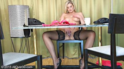Сексуальная блондинка в чулках мастурбирует пилотку за столом