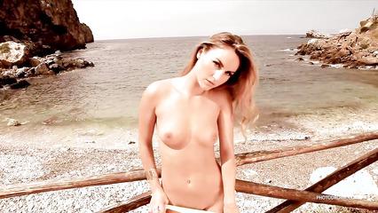 Длинноногая модель показывает на пляже задницу и красивые титьки