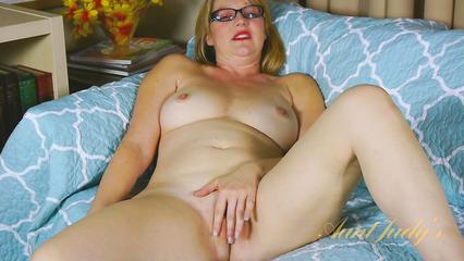 Зрелая блондинка в очках ласкает пальчиками промежность