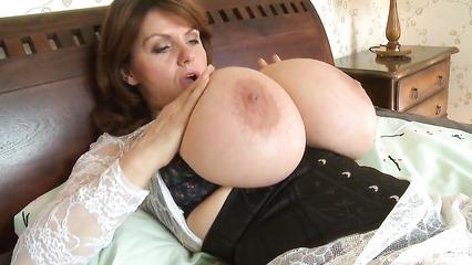 Развратная дамочка позирует в постели показывая громадные дойки