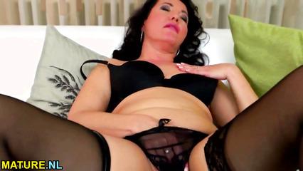 Зрелая дамочка в черных чулках страстно мастурбирует розовую пилотку