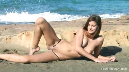 Симпатичная девушка с маленькими сиськами позирует голой на пляже