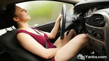 Хорошенькая брюнетка мастурбирует промежность в машине